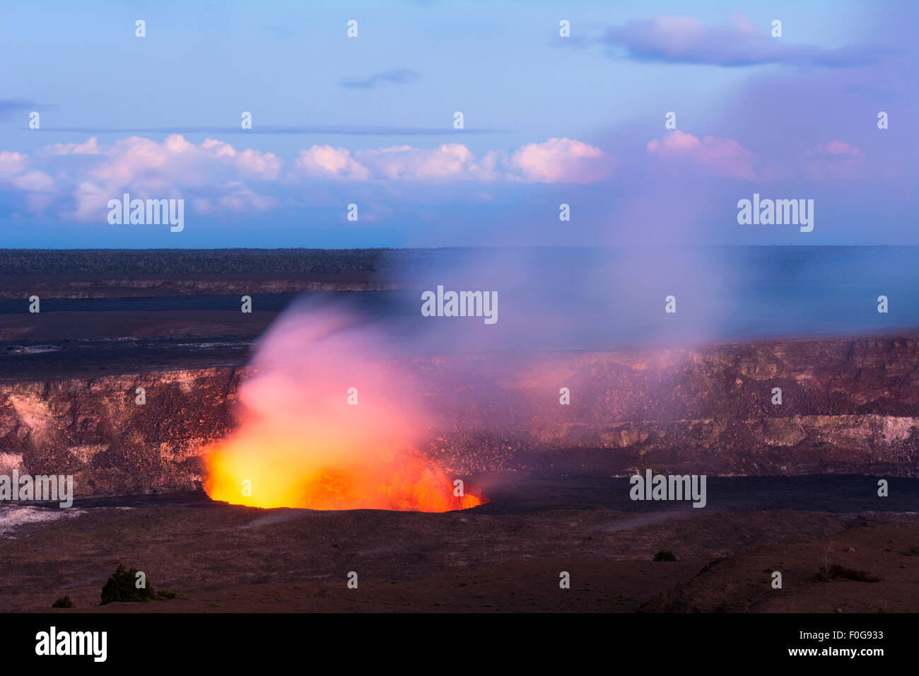 As the sun sets Kilauea volcano begins to show the hot lava glow of its active vent, spewing out smoke as the molten - Stock Image