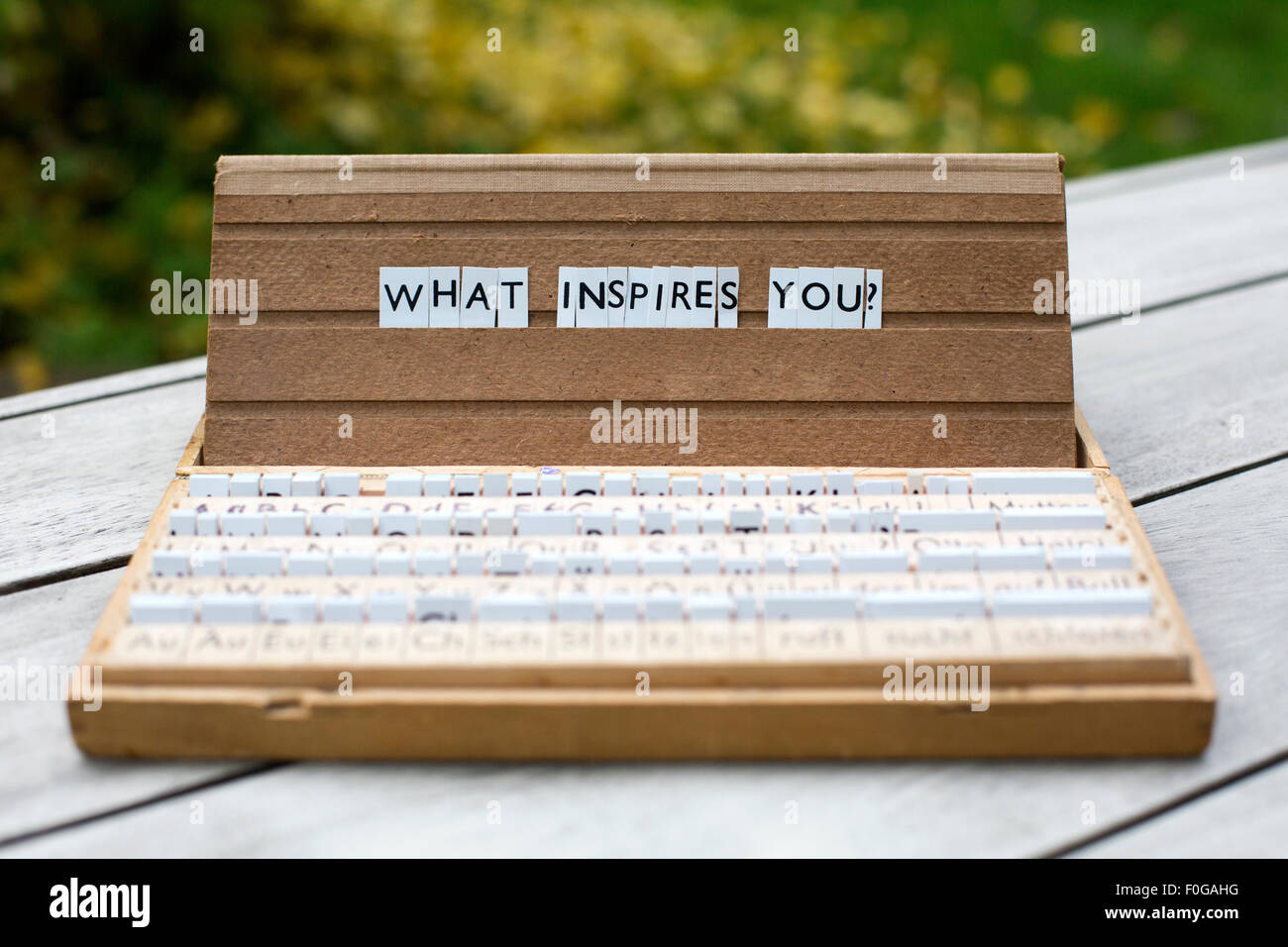 the words 'what inspires you?' on an old school letter box - Stock Image