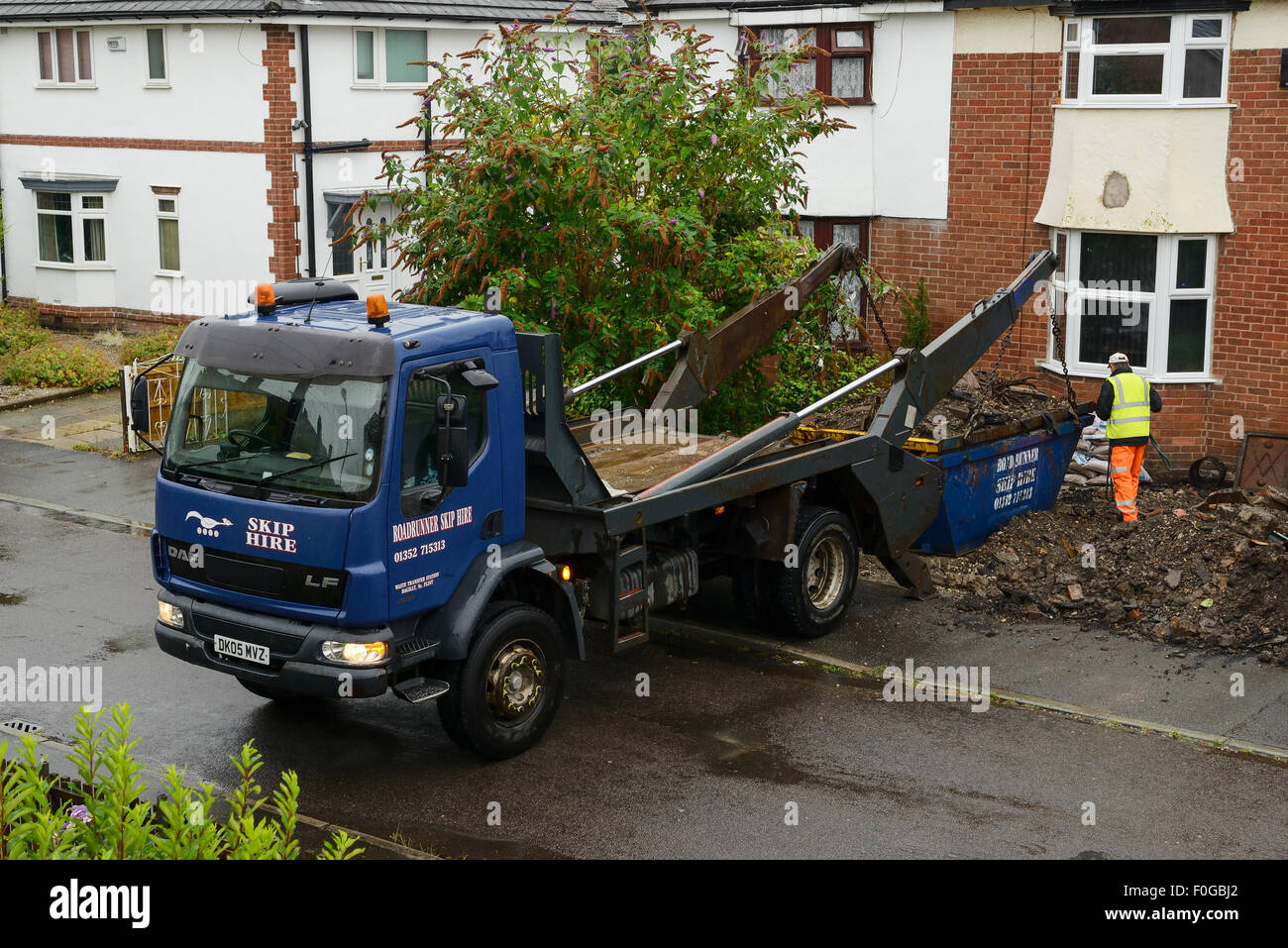 Vehicle collecting a skip from the front garden of a house - Stock Image