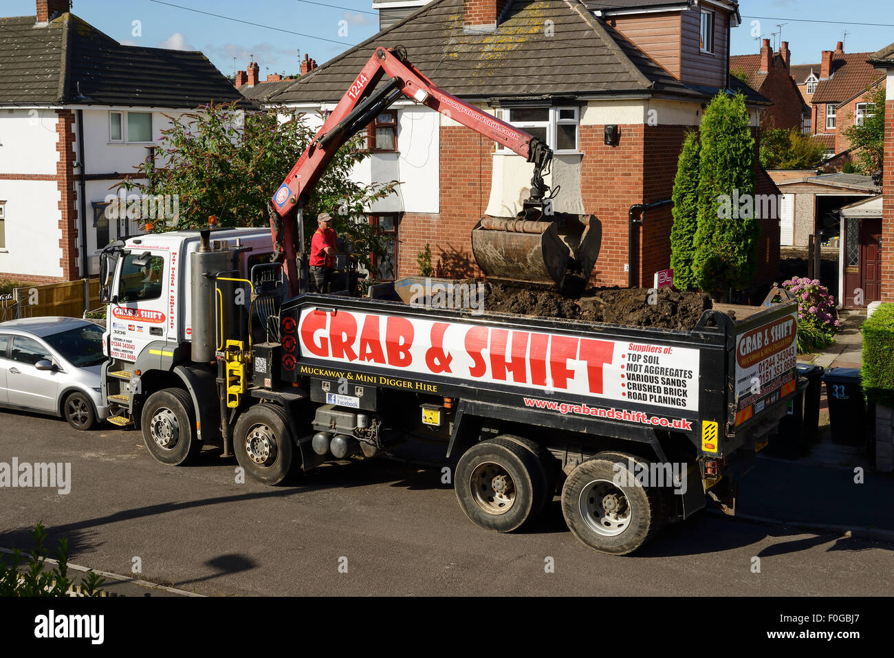 Grab and Shift vehicle collecting soil and muck from the front garden of a house - Stock Image