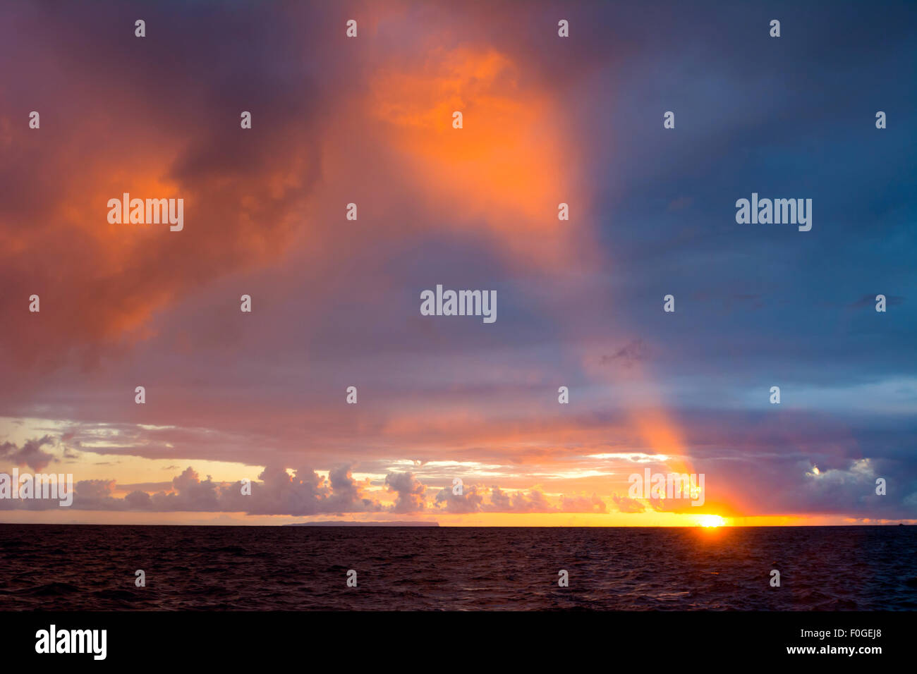 A sunset at Hanalei Beach in Kauai after a thunderstorm shows a beam of light piercing the dark clouds. - Stock Image