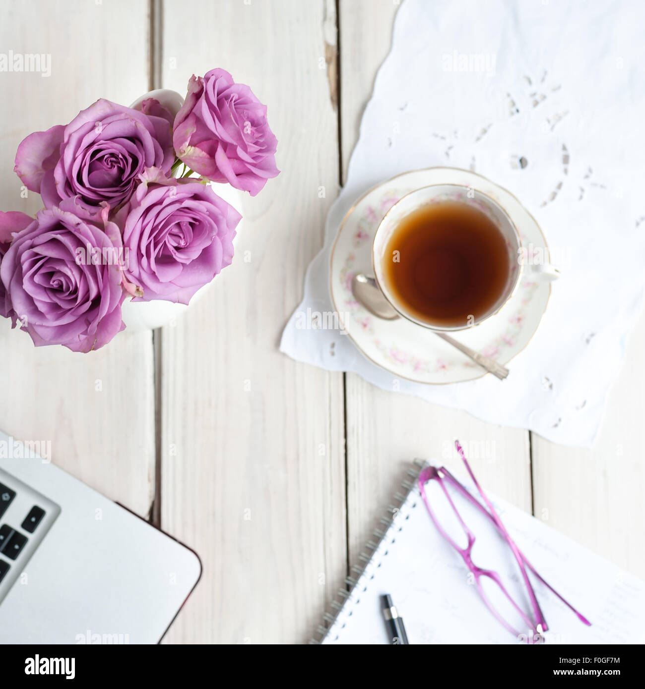 working at home tea break with roses laptop notebook glasses - Stock Image