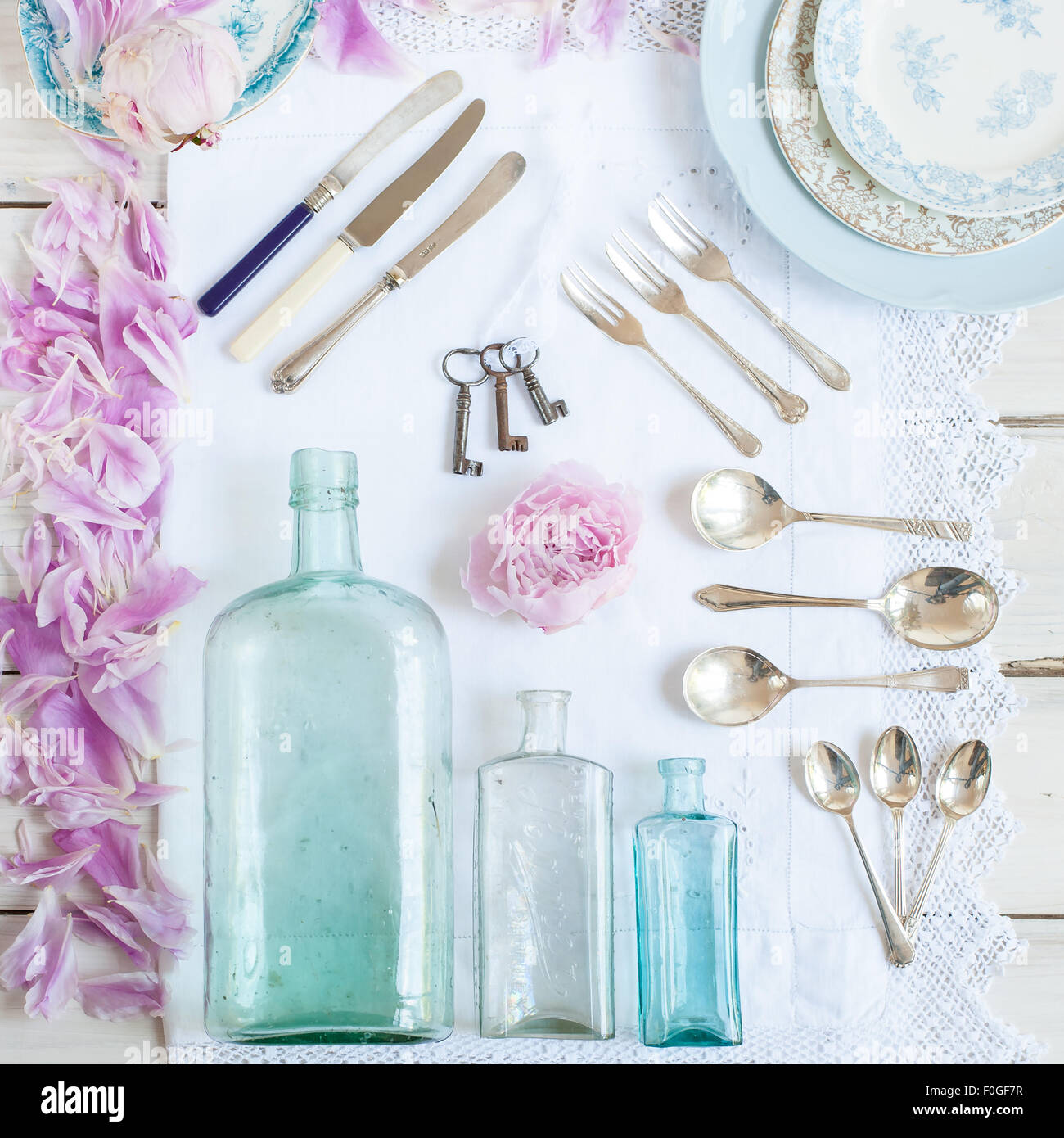 a collection of vintage bottles,  cutlery, plates, old keys, and peonies - Stock Image