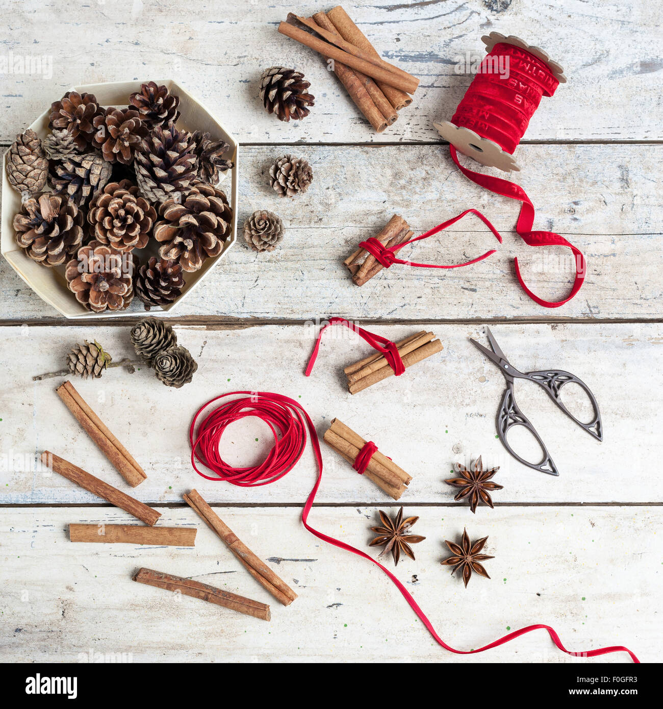 pinecones, spices and cinnamon bundles tied with red ribbon for Christmas - Stock Image