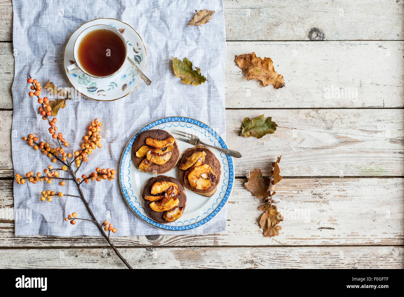pancakes with caramelised apples on vintage plate, with tea in vintage teacup, oak leaves and ilex berries Stock Photo