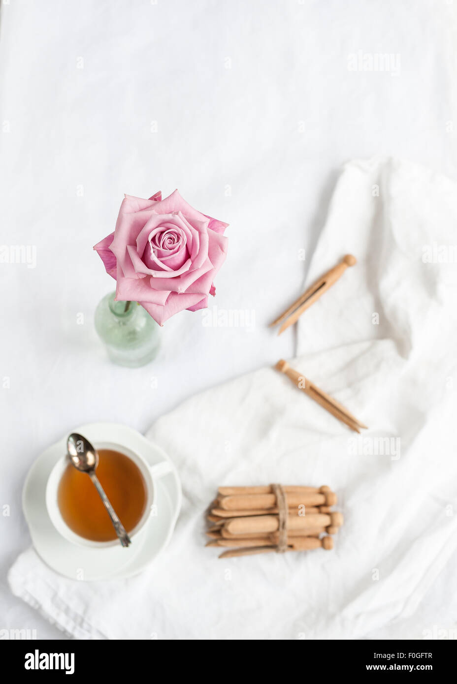 a single pink rose in focus, with blurred background of white fabric, teacup with teaspoon, and dolly clothes pegs - Stock Image