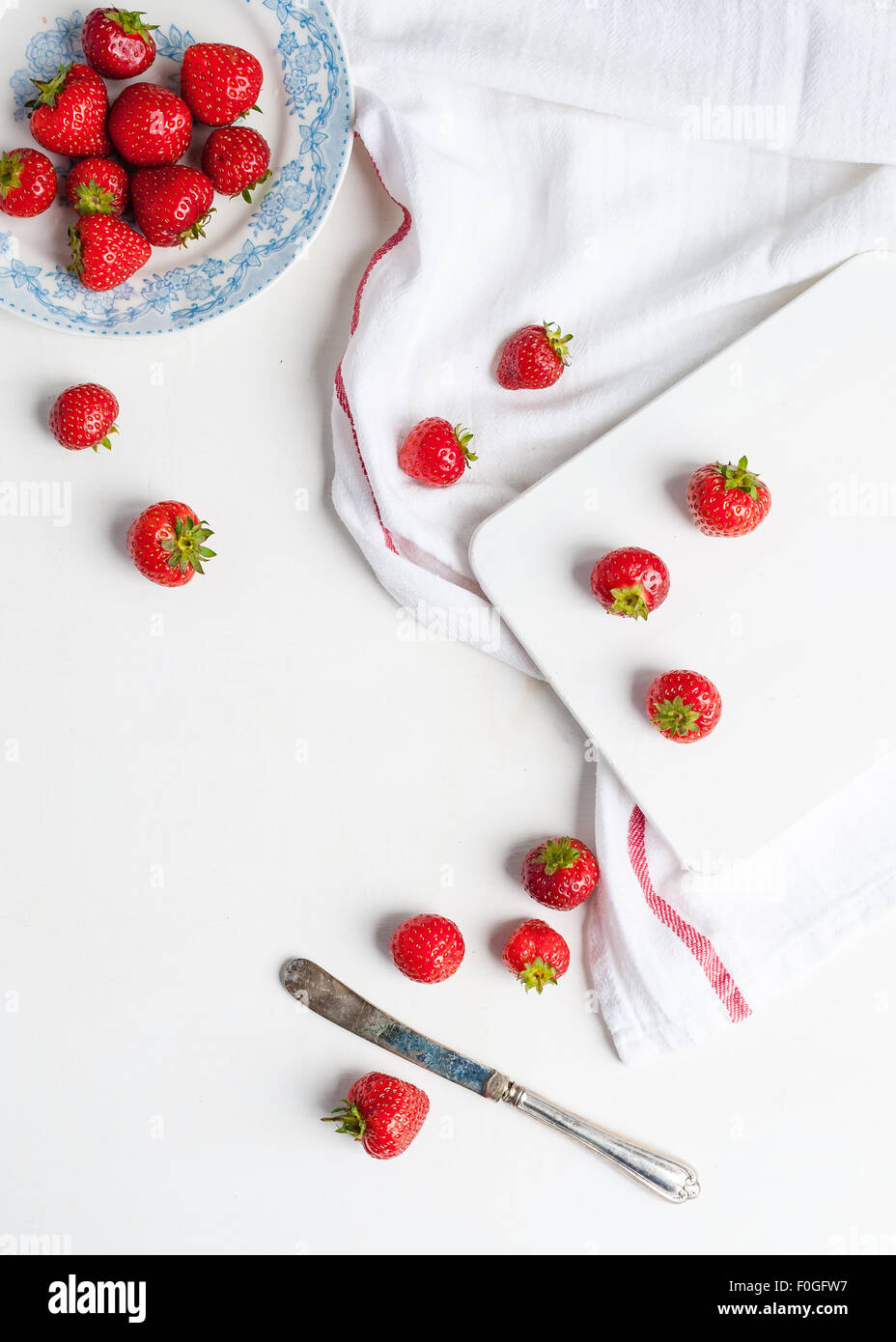 strawberries in a blue and white plate and on the table and chopping board - Stock Image