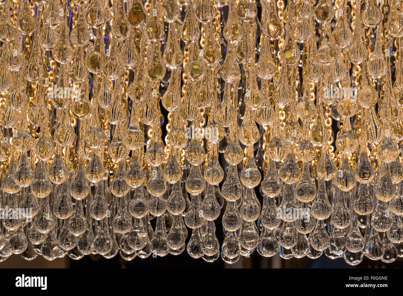 Backlit teardrop shaped glass beads of a chandelier glow at a lamp shop in the Grand Bazaar, Istanbul, Turkey. - Stock Image