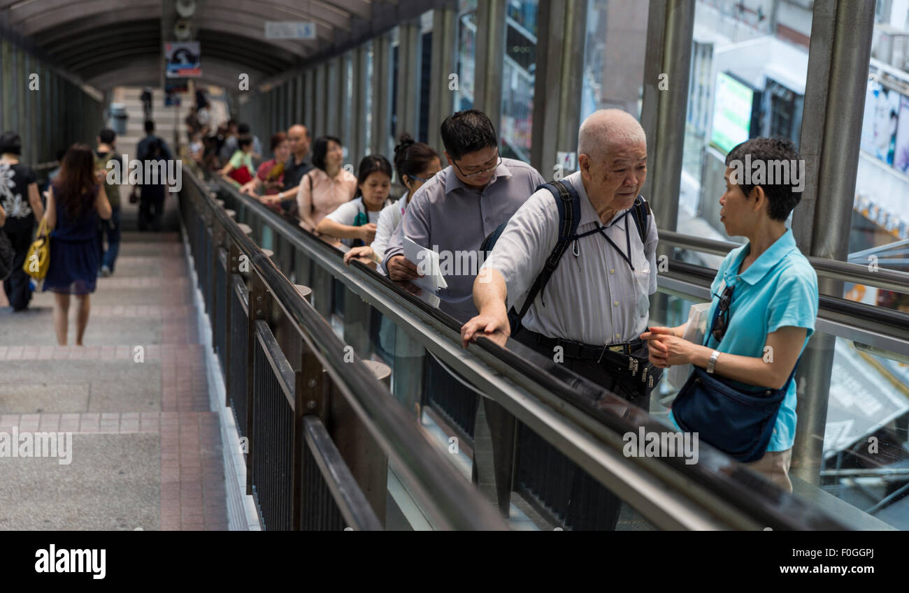 Pedestrians ride the Mid-Level escalators up the steep hill of the Central district of Hong Kong Island. Others - Stock Image