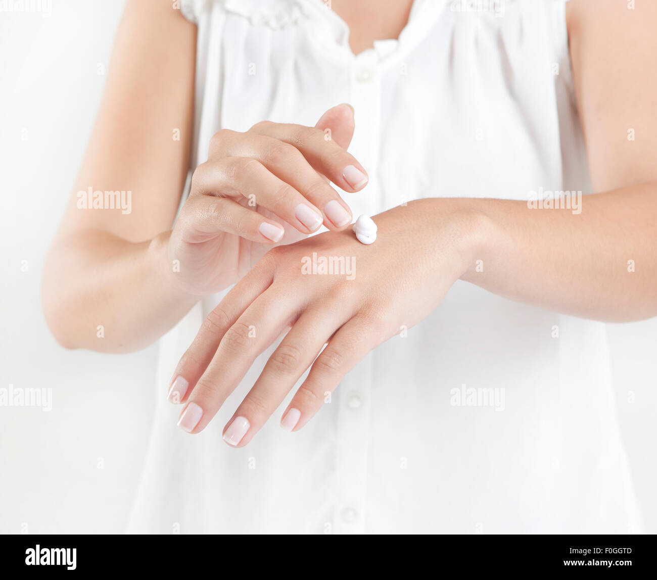 a woman with cream on hands, a face - Stock Image