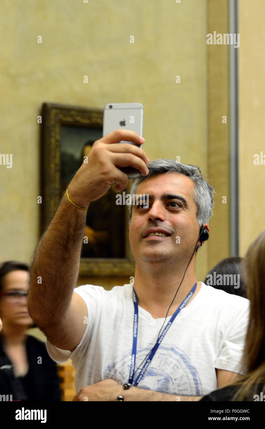 A man gets a selfie with the Mona Lisa. Stock Photo