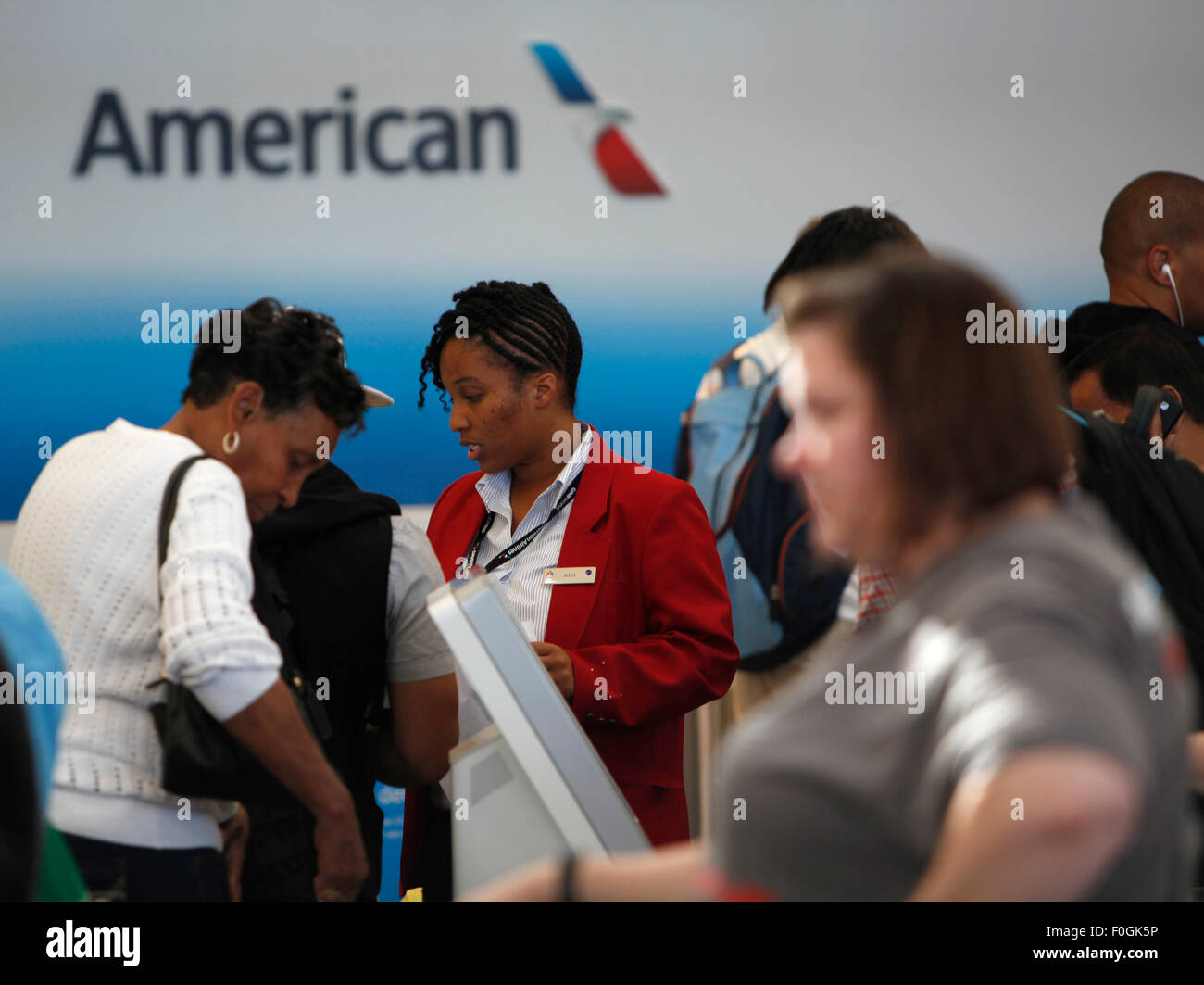 Washington, DC, USA. 15th Aug, 2015. An American Airline staff helps passengers check in at Ronald Regan National - Stock Image