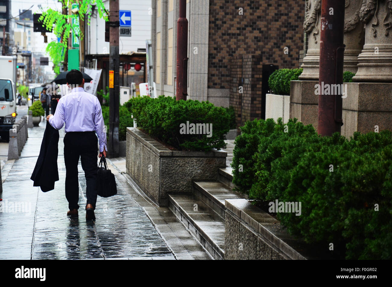 Bussiness japanese man walking go to office near at Nara station while raining time on July 7, 2015 in Nara, Japan Stock Photo