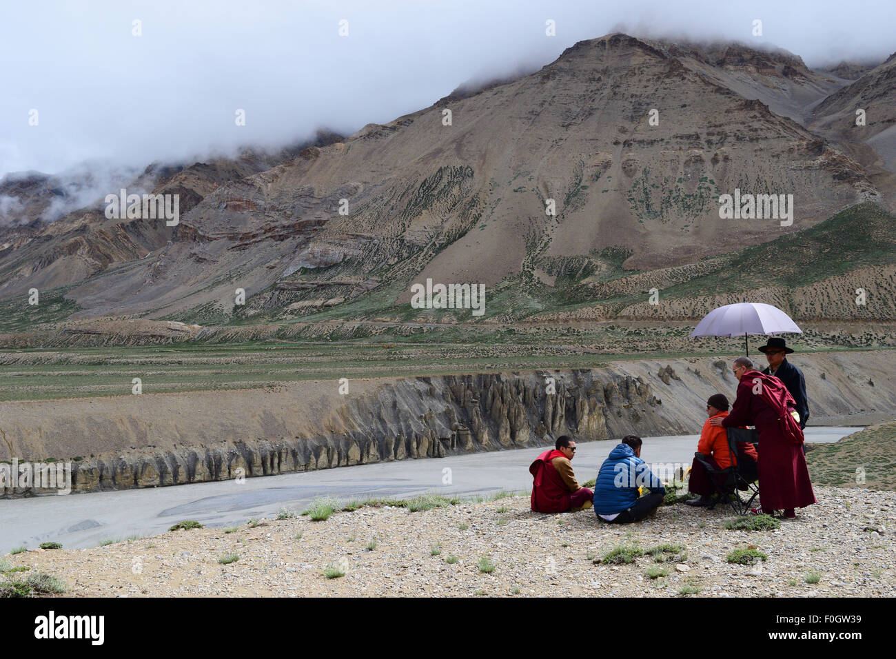 Buddhist Monks relaxing in Himalayas Mountains near frozen himalaya river in Leh Ladakh India - Stock Image