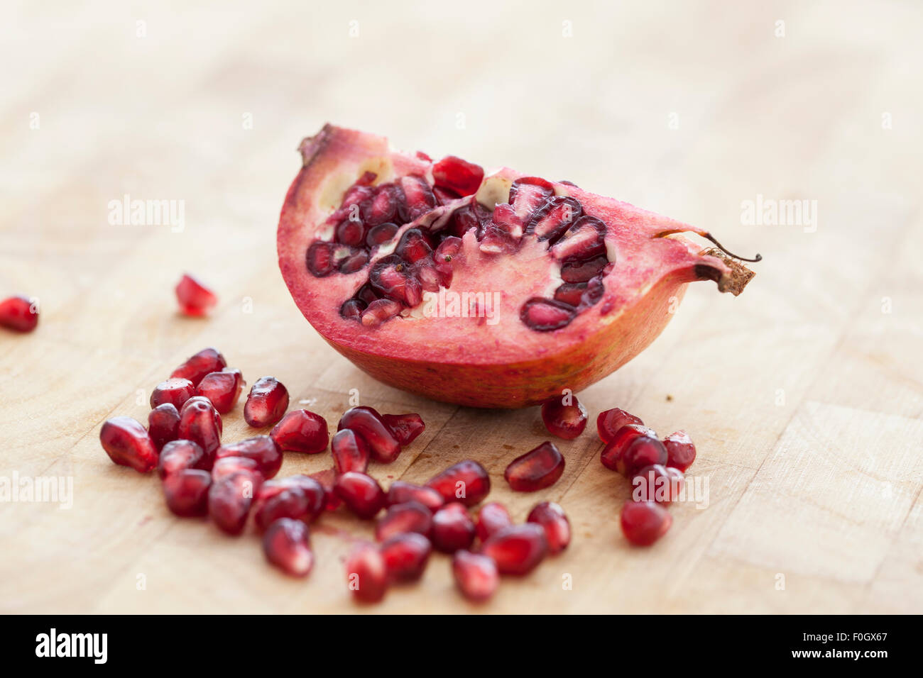 A sliced pomegranate with seeds or arils photographed on a wooden surface with window light. - Stock Image