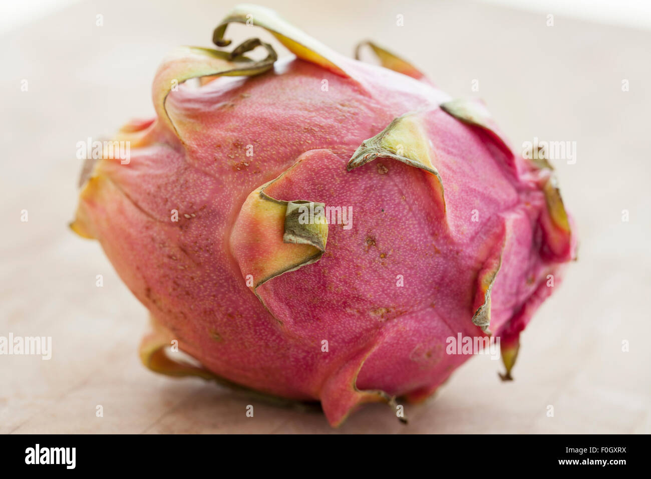 A dragon fruit or pitaya on a wooden surface photographed with window light. - Stock Image
