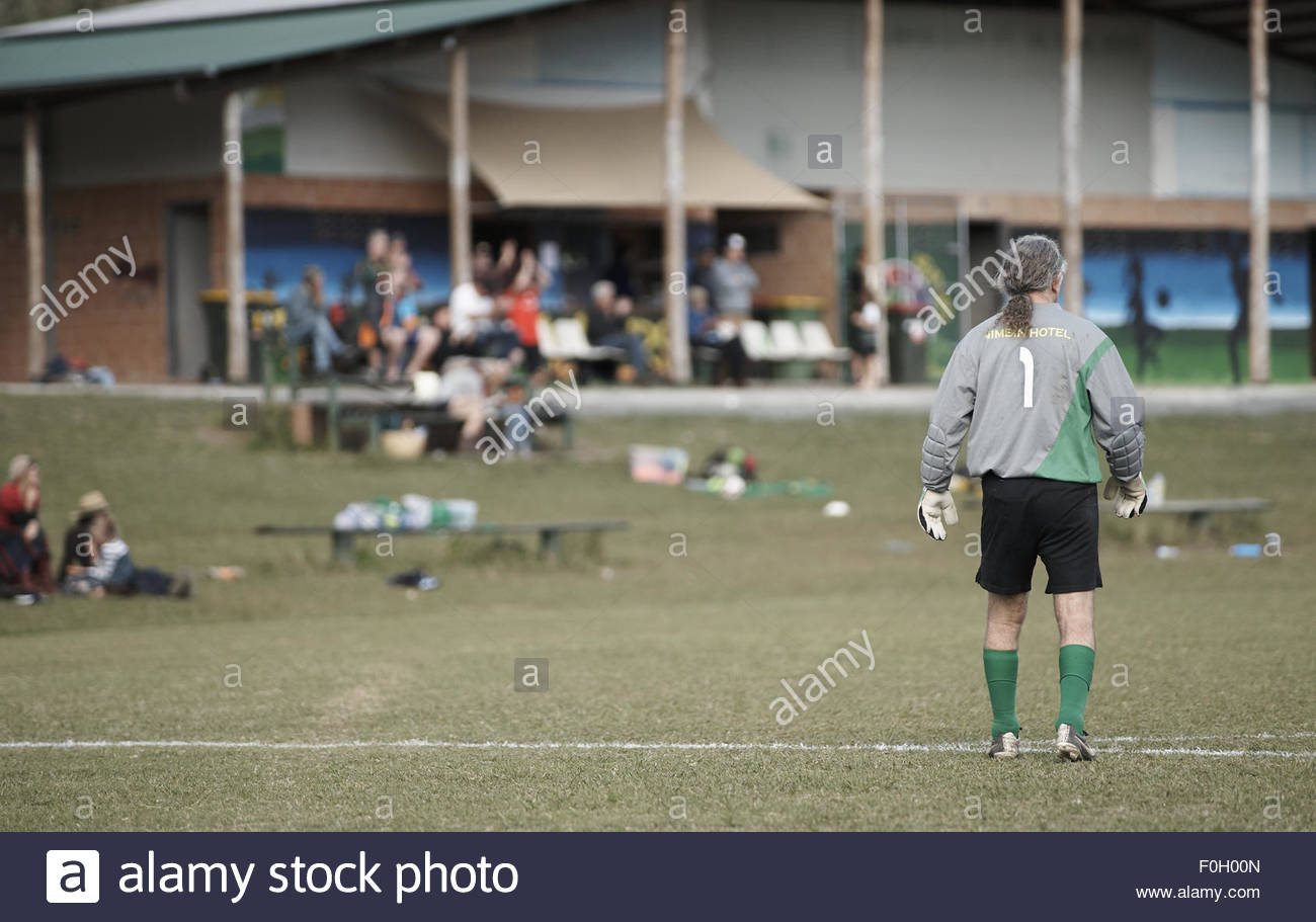 the goalkeeper stands alone, watching and waiting; during a weekend football match, at the nimbin headers soccer - Stock Image