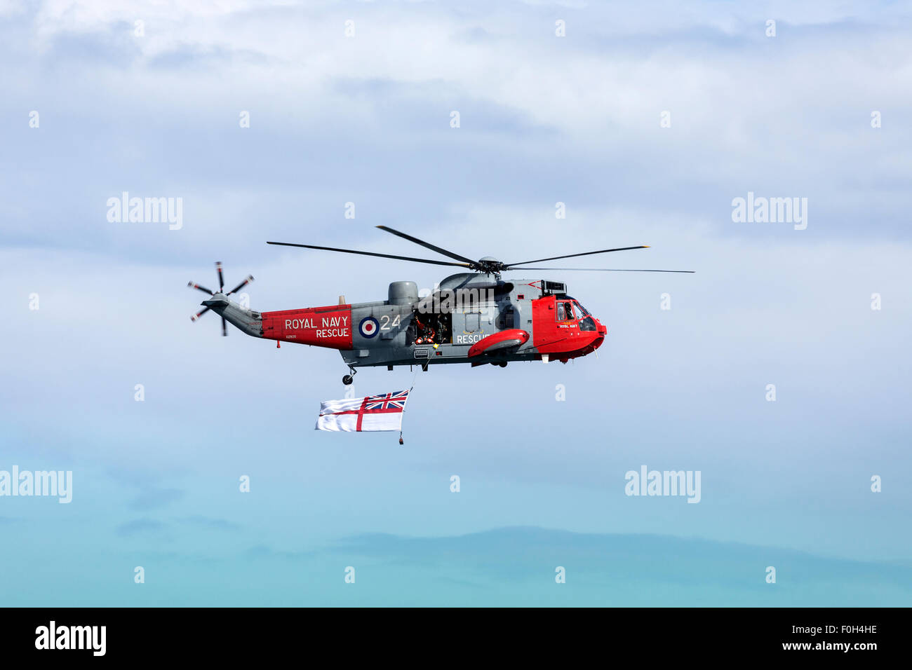 A Royal Navy Search and Rescue helicopter flying the White Ensign off the northeast coast of the United Kingdom. - Stock Image
