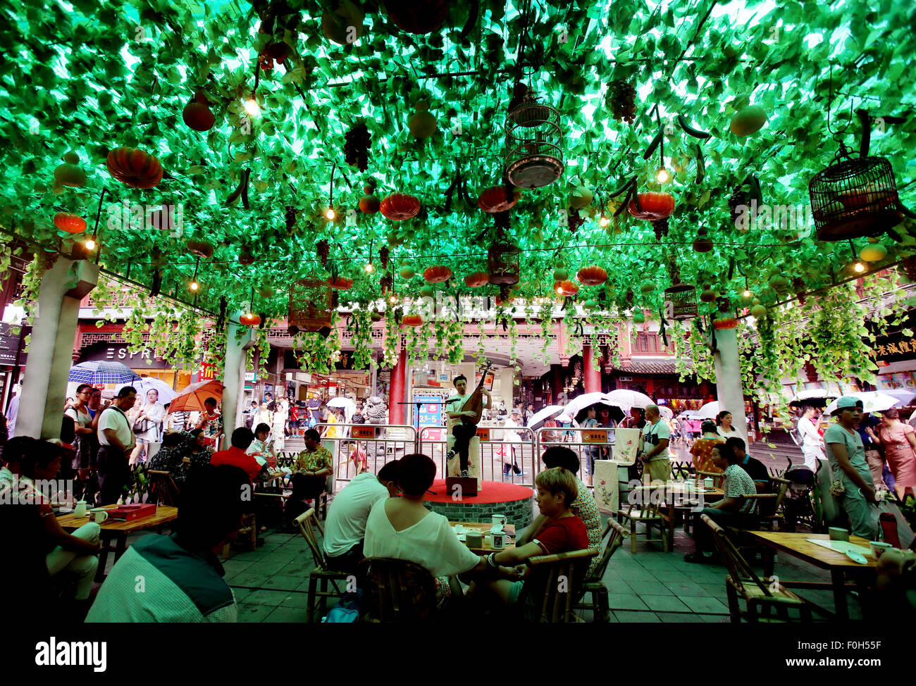 Shanghai, China. 16th Aug, 2015. Tourists watch ballad singing performance at a night fair in Yu Garden of Shanghai, - Stock Image