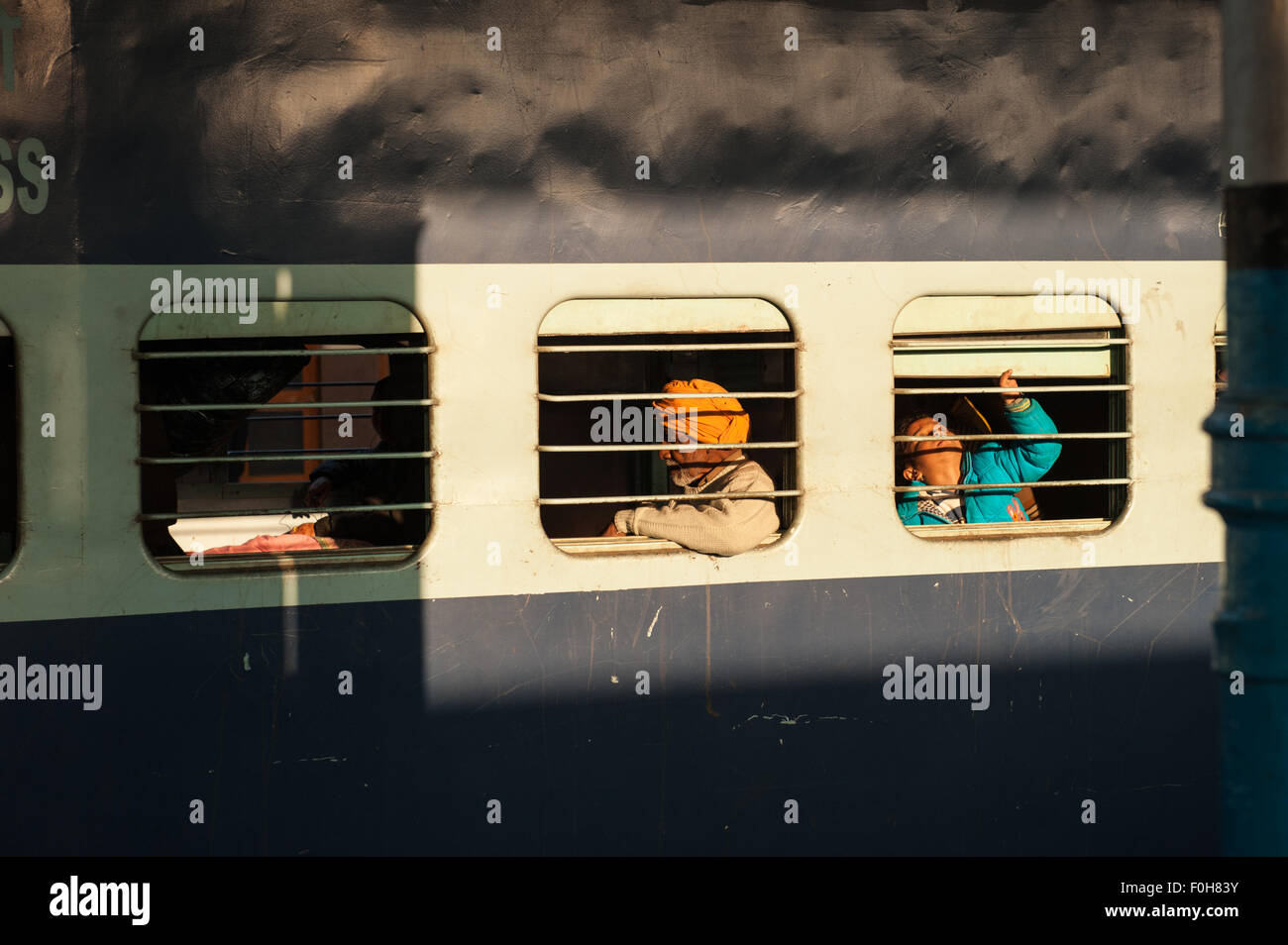 Kalka, Himachal Pradesh, India. passengers on a mainline train through barred windows. - Stock Image