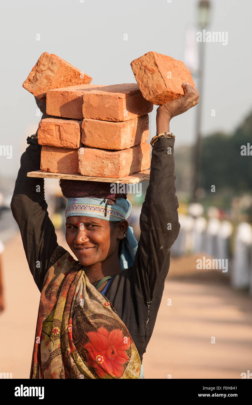 Delhi, India. Woman worker carrying eight bricks on her head, smiling. - Stock Image