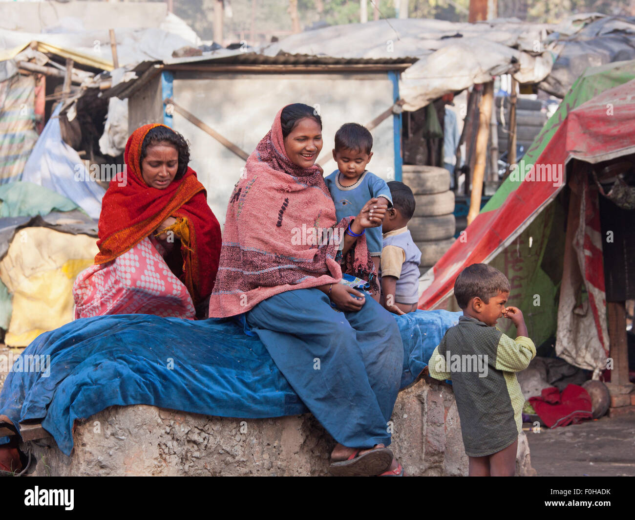 Residents of a makeshift settlement on the edge of Varanasi. Shanty towns such as this are common across Indian - Stock Image