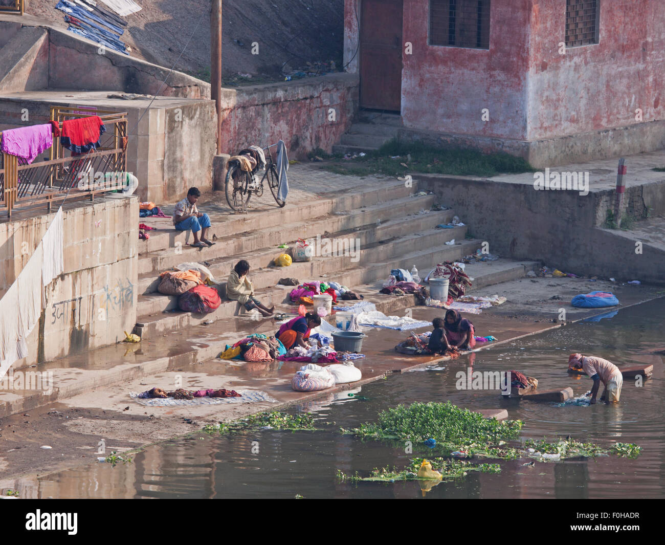 People washing clothes at a ghat on the Varuna river, common practice across India as many do not have access to - Stock Image