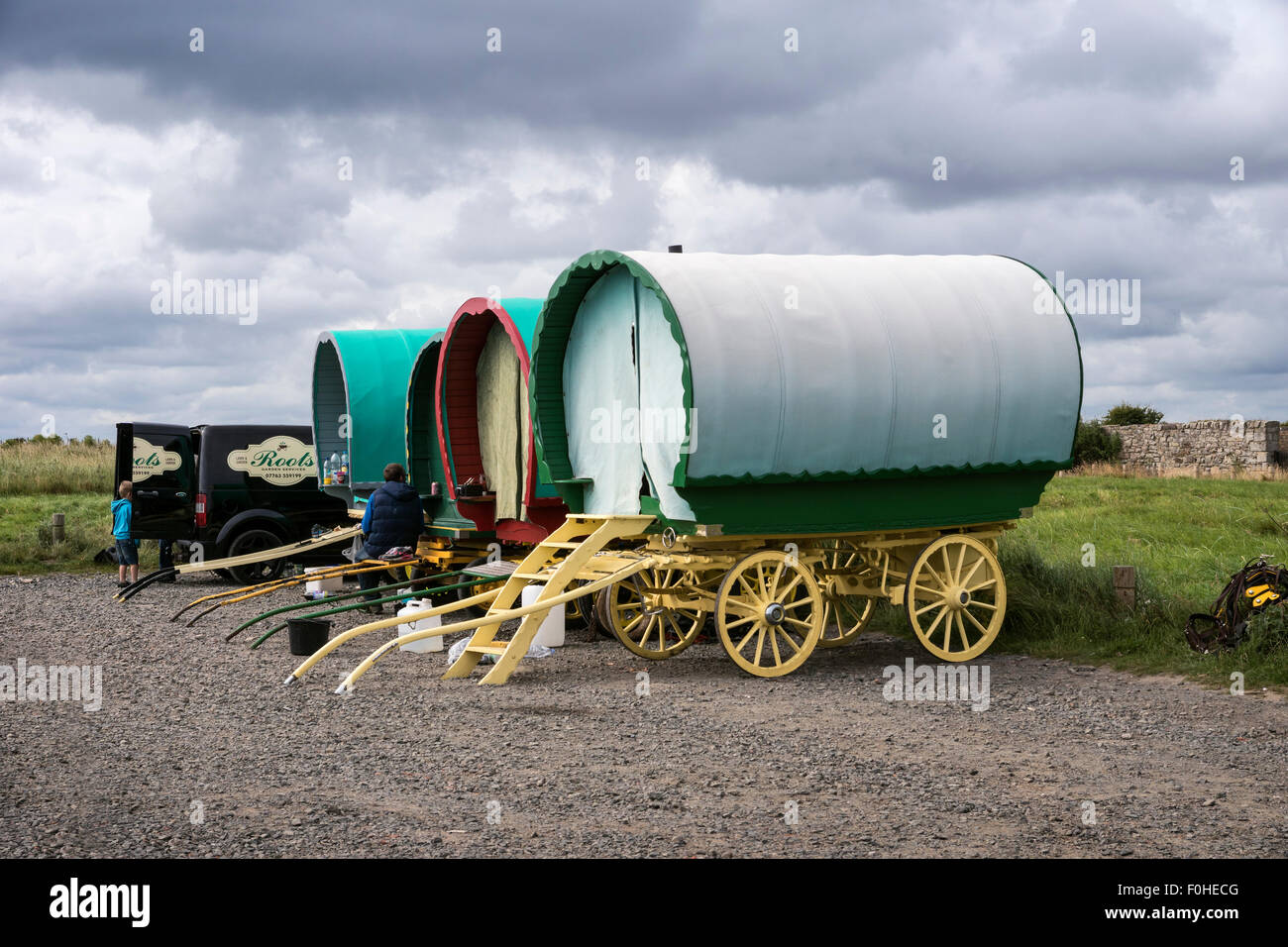 Bow top caravans temporarily camped in the car park at Boulmer in Northumberland - Stock Image