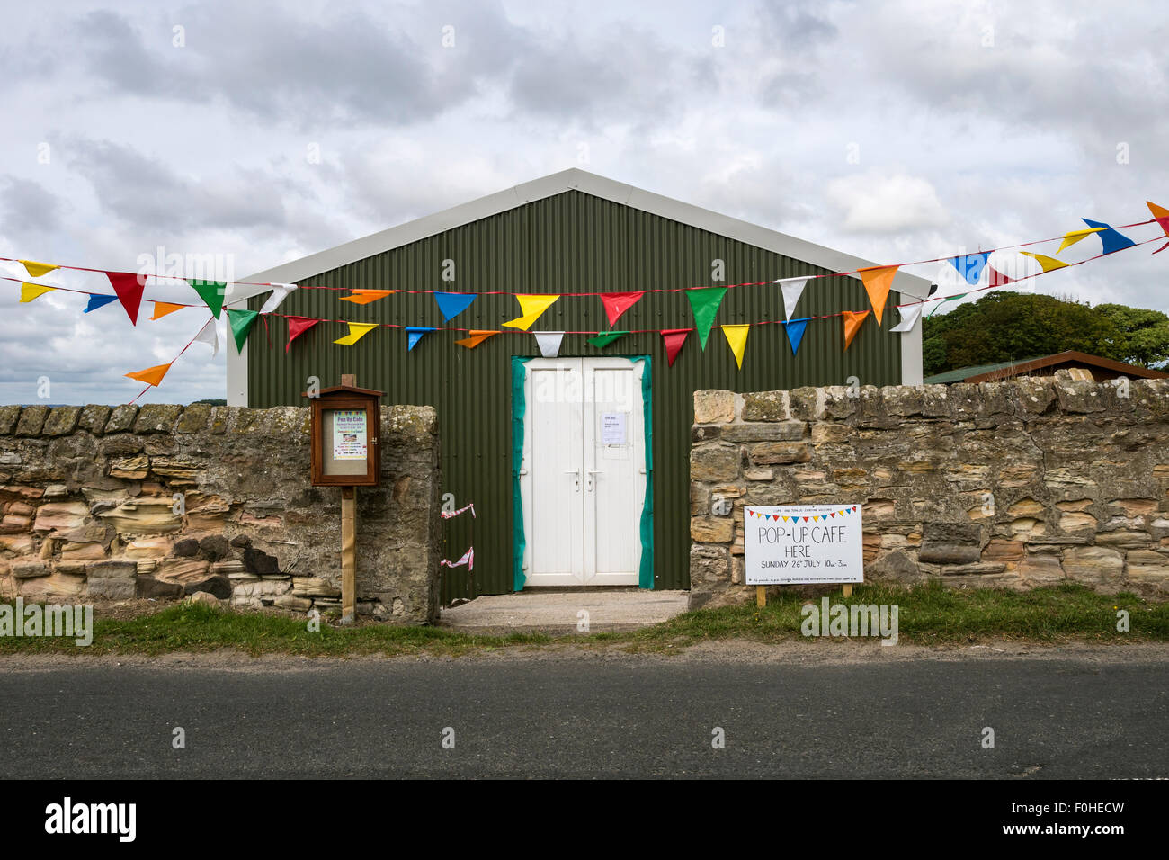 Village hall at Boulmer in Northumberland with sign advertising a pop-up cafe. - Stock Image