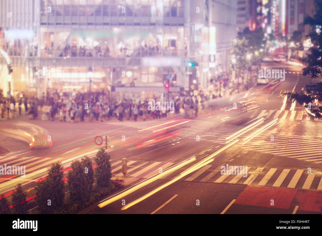 People and vehicles cross the  famously busy Shibuya intersection in Tokyo - Stock Image