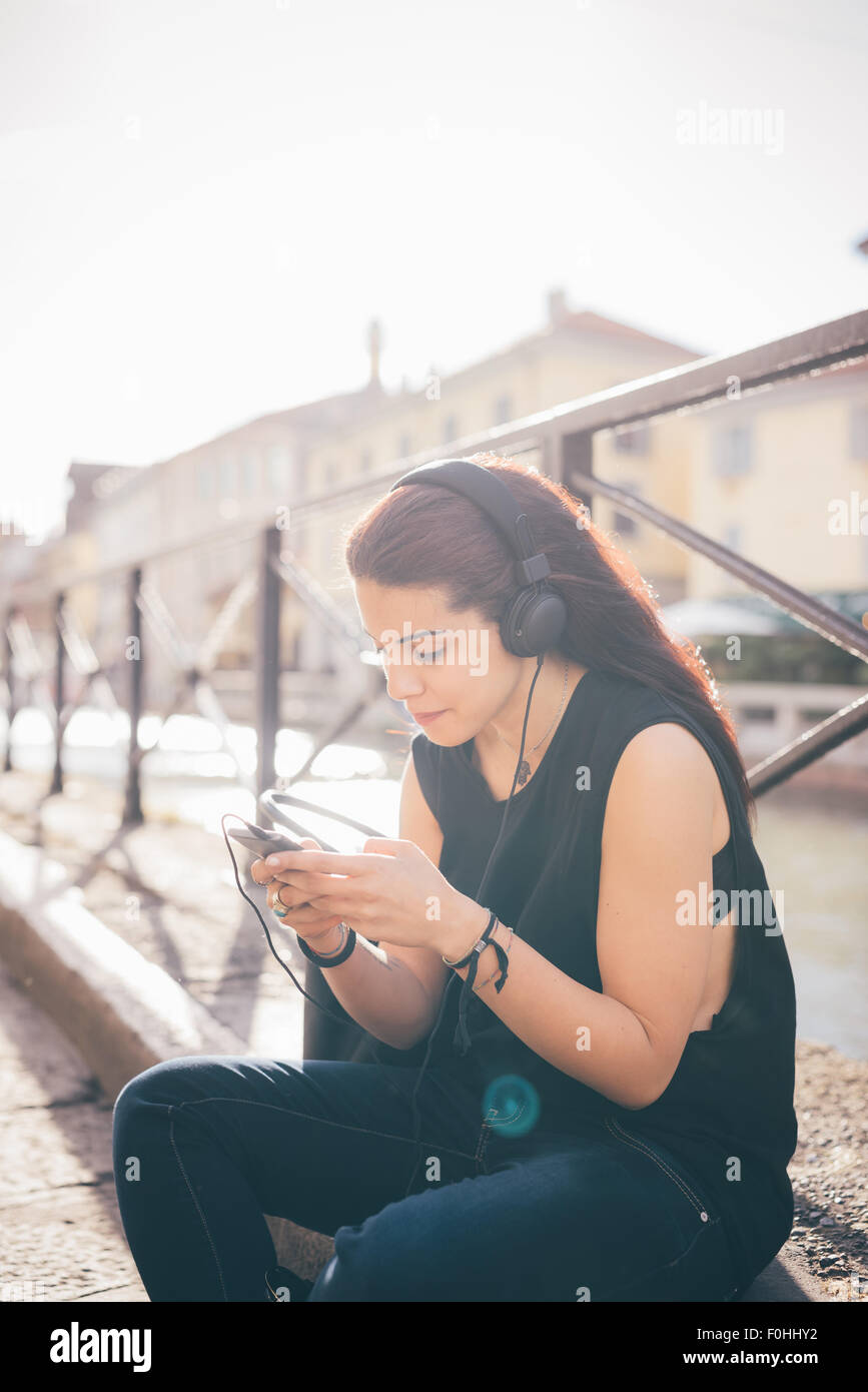 Young beautiful reddish brown hair caucasian woman listening to the music seated on the sidewalk - relax, music, - Stock Image