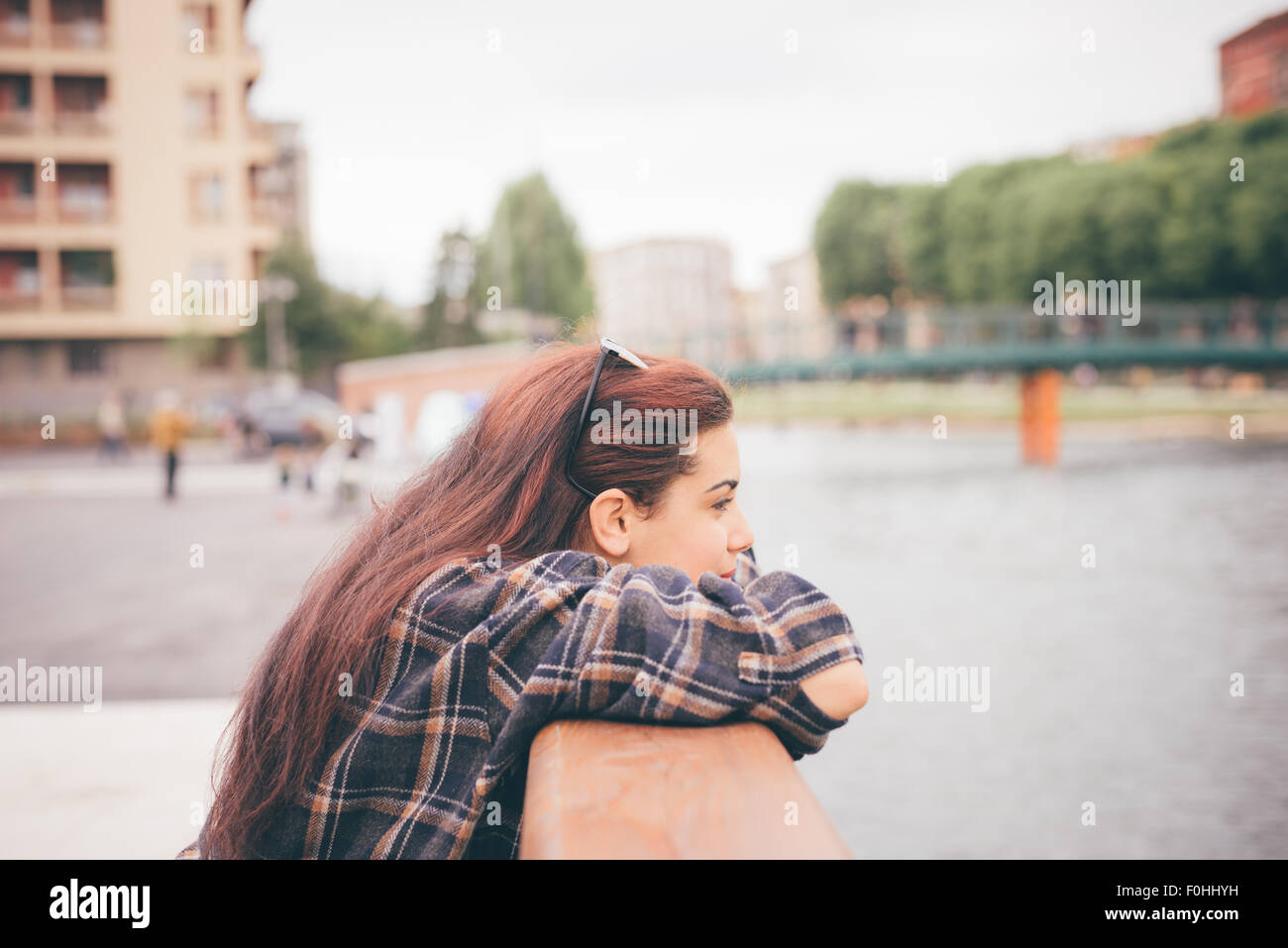 Half length of a young beautiful reddish brown hair caucasian girl leaning against a windowsill overlooking - pensive, Stock Photo