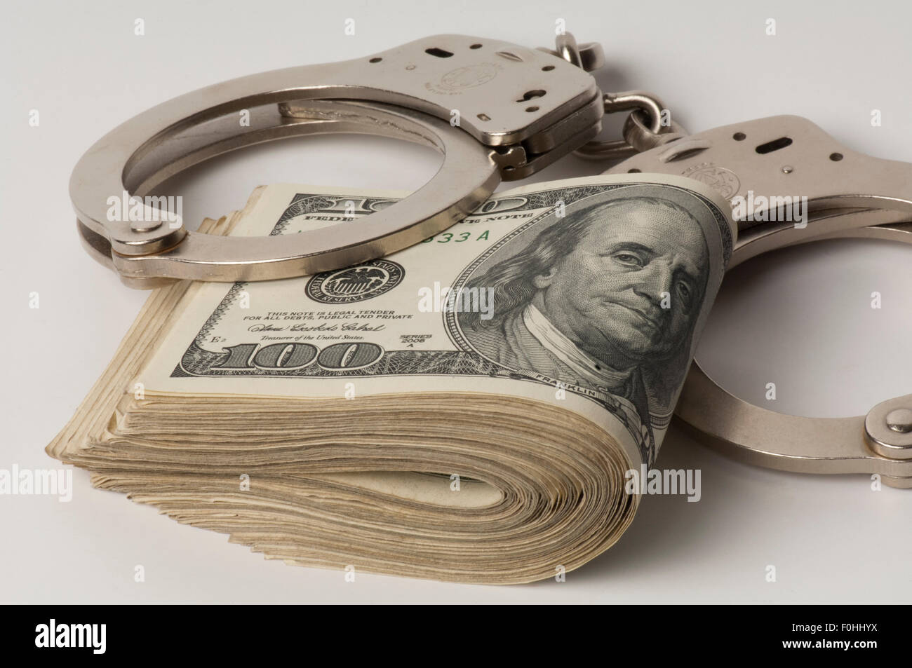 handcuffs on wad of United States $100 dollar bills - Stock Image