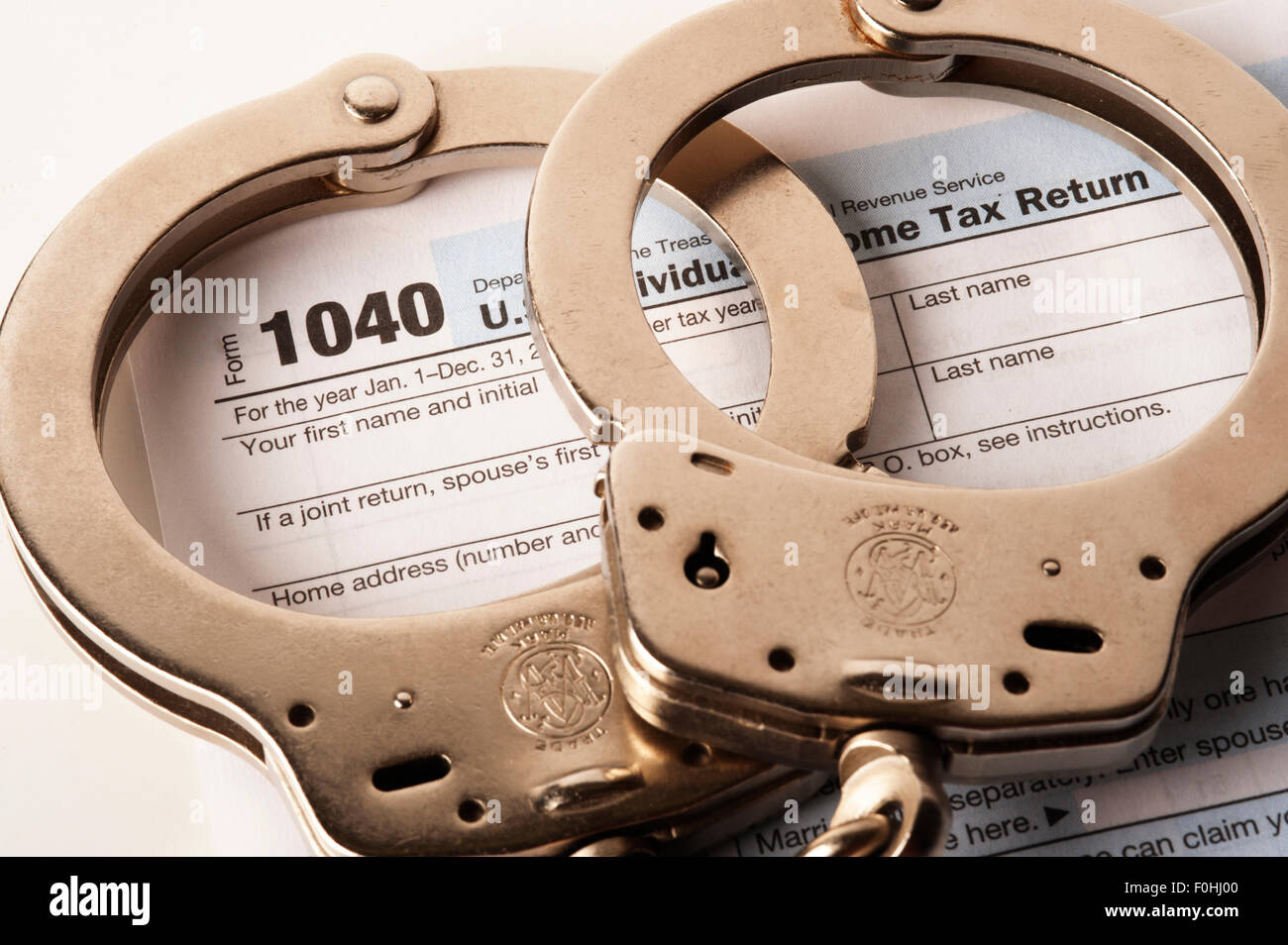 handcuffs on United States tax return 1040 warning on cheating - Stock Image