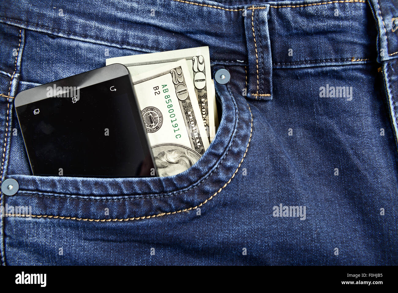 Money and smartphone in the pocket of jeans - Stock Image