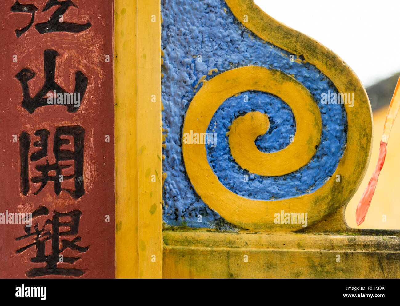 Detail of multicolored gate of Dinh Cam Pho Communal Hall, Hoi An, Vietnam, with yellow scroll and Chinese writing - Stock Image