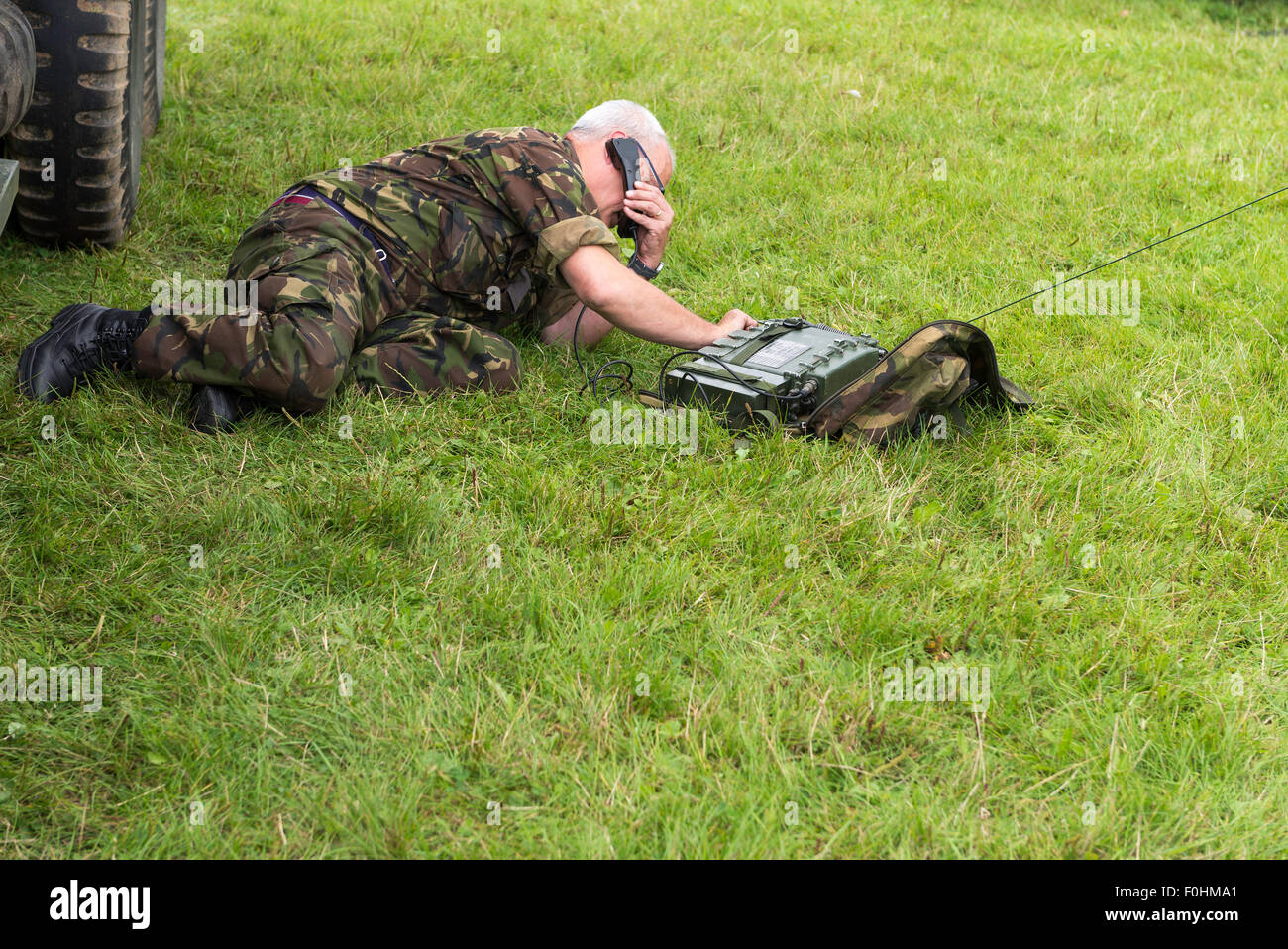 Man dressed in camouflage army uniform laying on ground using army radio telephone - Stock Image
