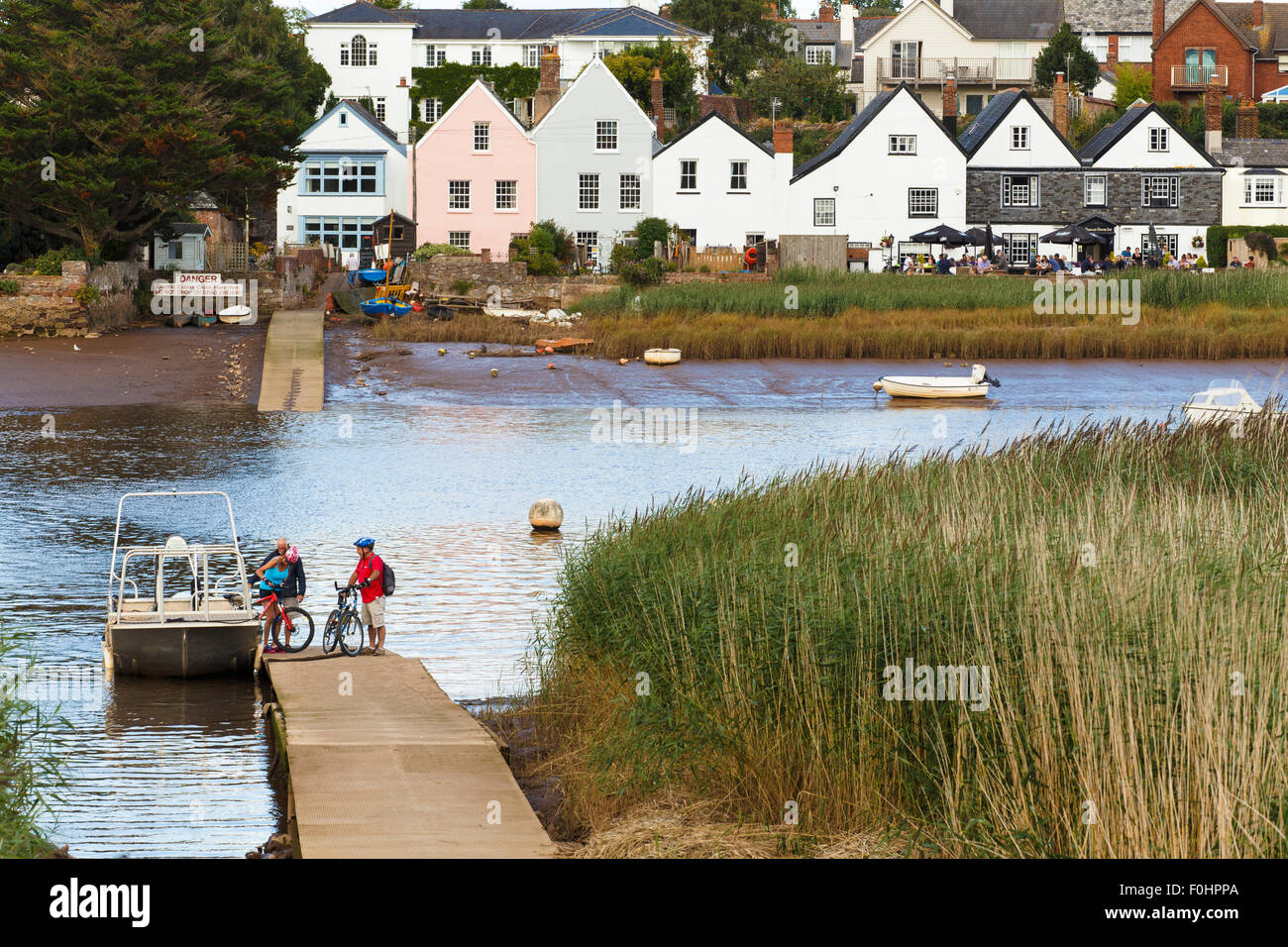 Mature couple disembarking from small ferry across river Exe at Topsham in Devon. - Stock Image