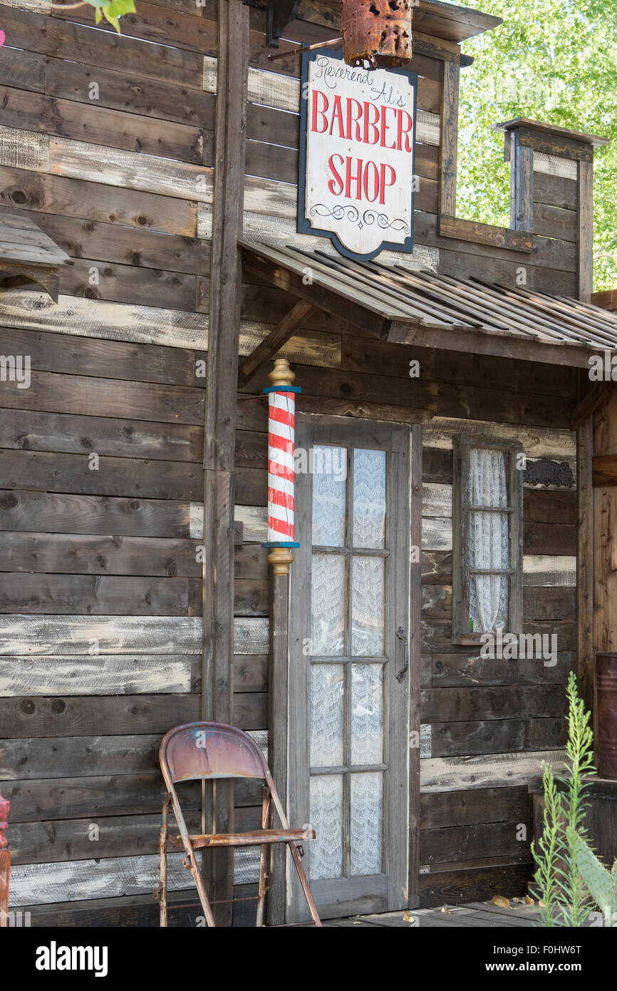 Wild west style Barbers shop exterior facade with red sign and red and white barbers pole in Joshua tree California - Stock Image