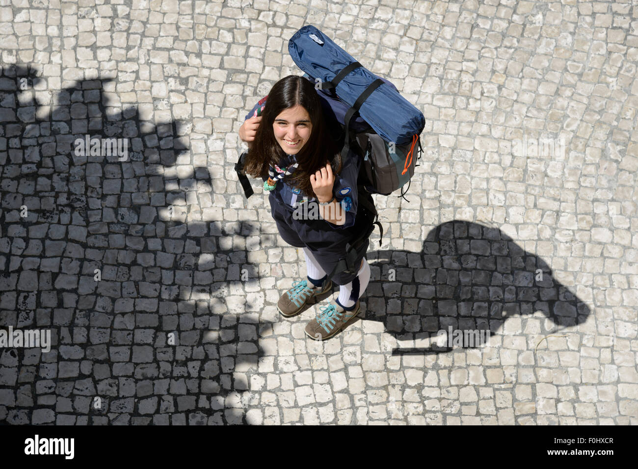 Portrait of a girl scout in scouting uniform wearing a backpack viewed from above - Stock Image