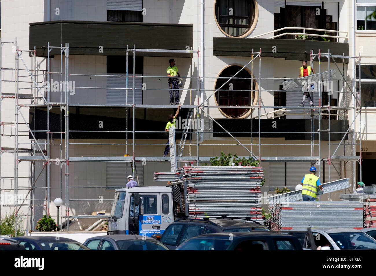 Construction workers installing scaffolding on a building - Stock Image