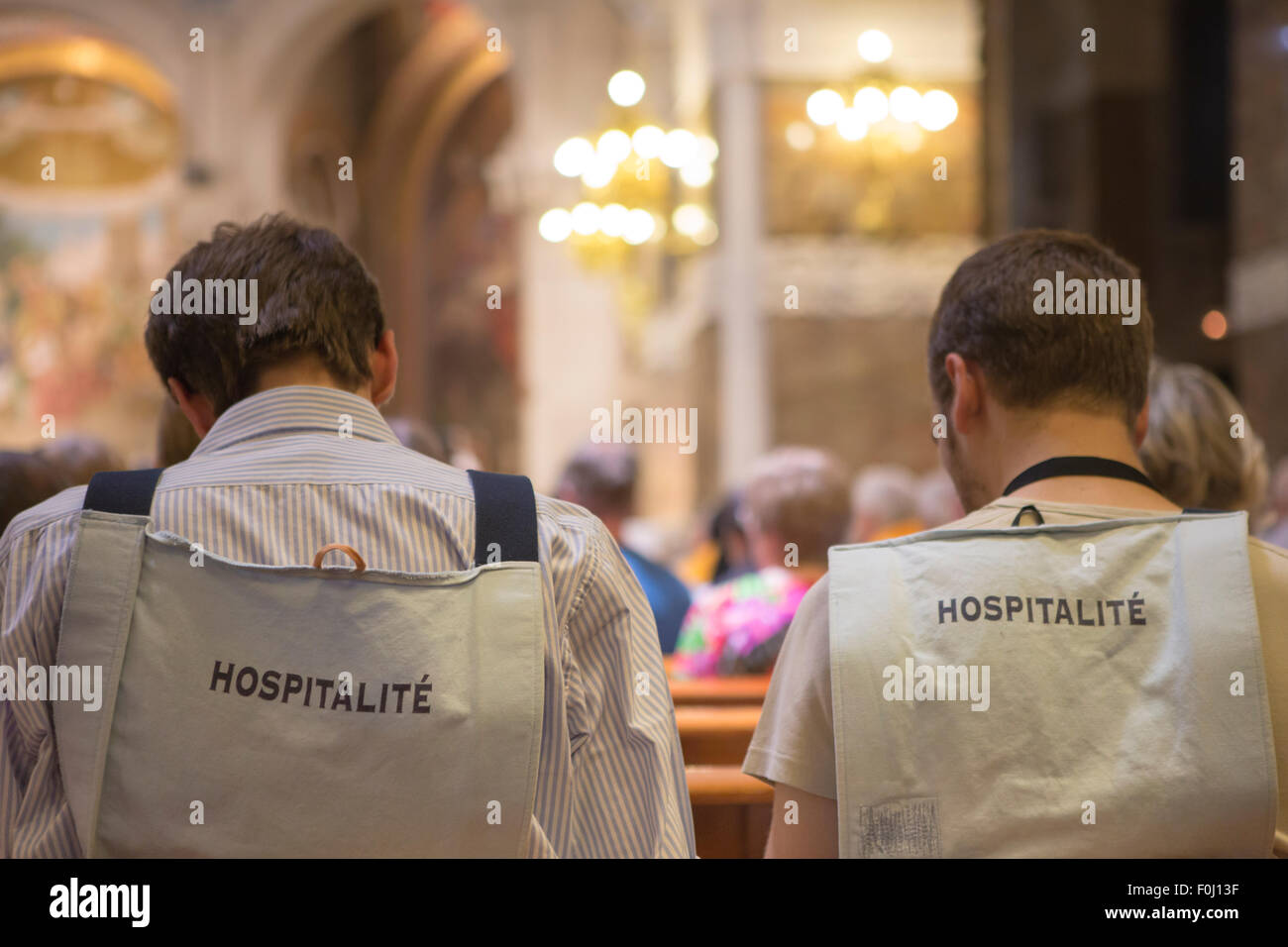 Back of volunteers in Lourdes in the church. Volunteer helpers in Lourdes are welcoming and friendly. The Hospitality - Stock Image