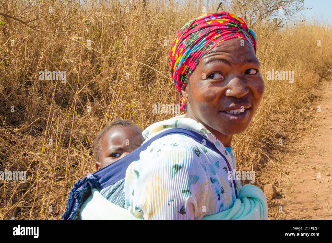 A mother carries her young son on her back as she hikes through the dirt roads of rural Swaziland. Stock Photo