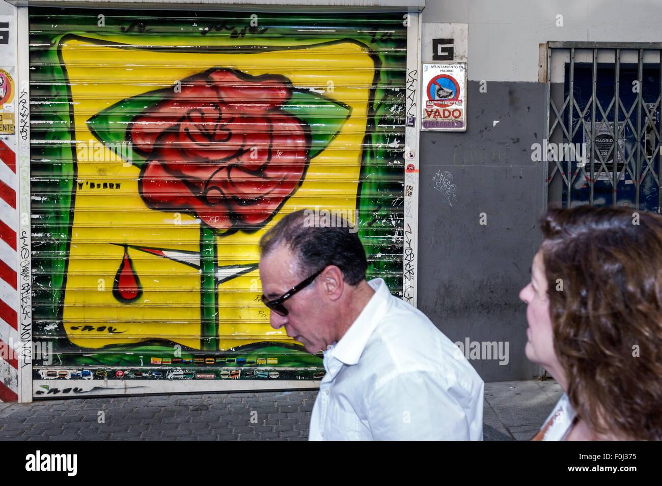 Madrid Spain Europe Spanish Centro Lavapias Calle de Zurita mural rose thorn blood Hispanic man woman pedestrian - Stock Image