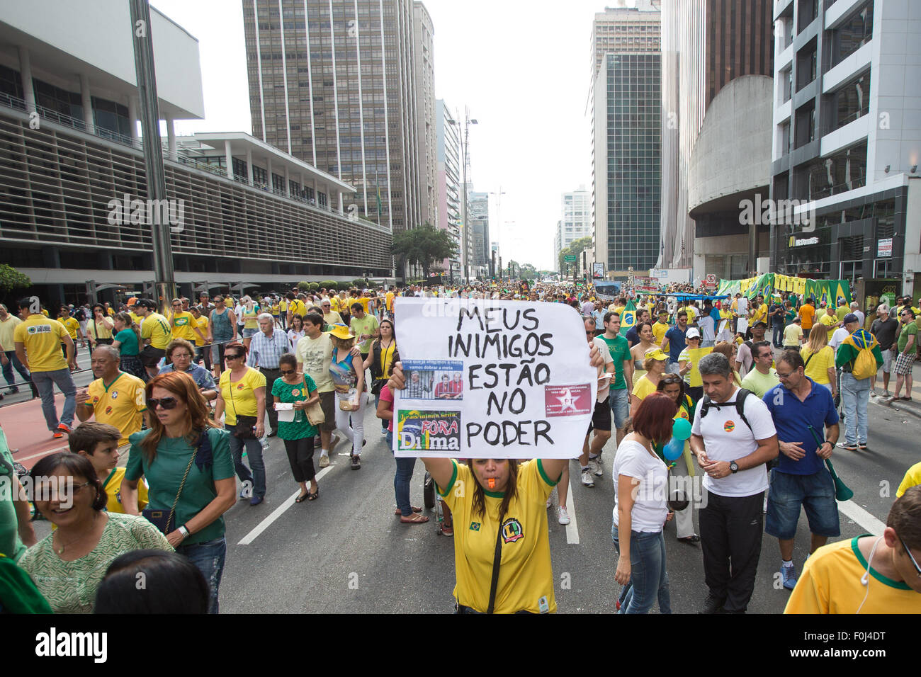 Sao Paulo, Brazil. 16th Aug, 2015. A protester holds a cardboard with the slogan 'my enemies are in power' - Stock Image