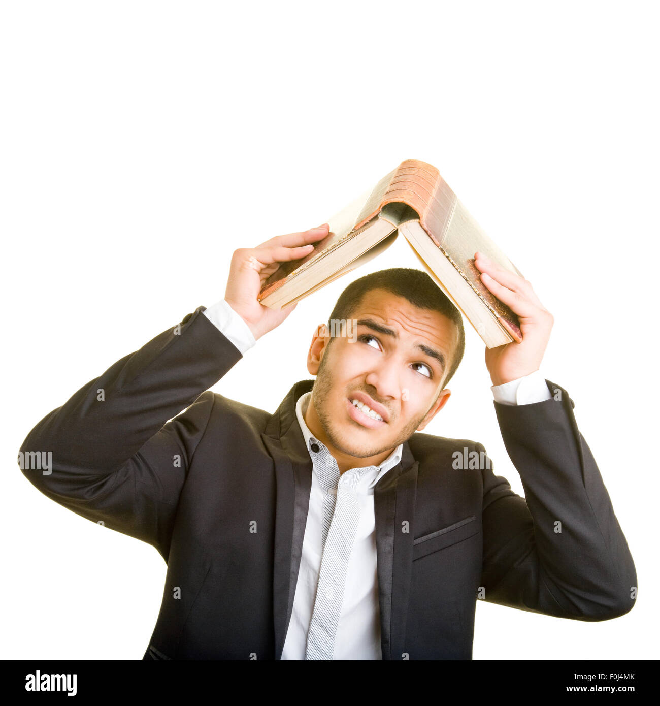 Fearful man using a book as protective roof over his head - Stock Image