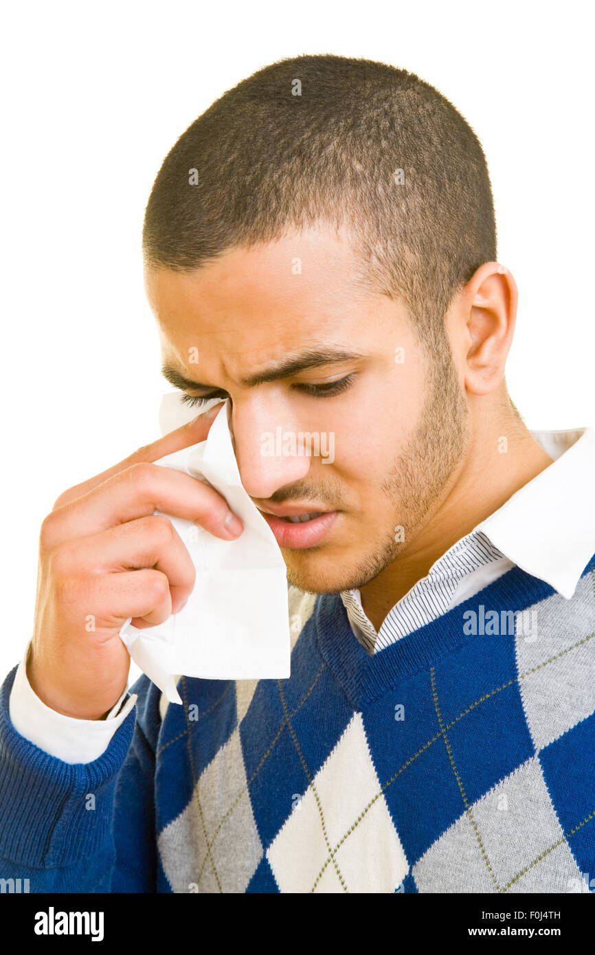 Young man crying and drying his tears with a paper handcherchief - Stock Image