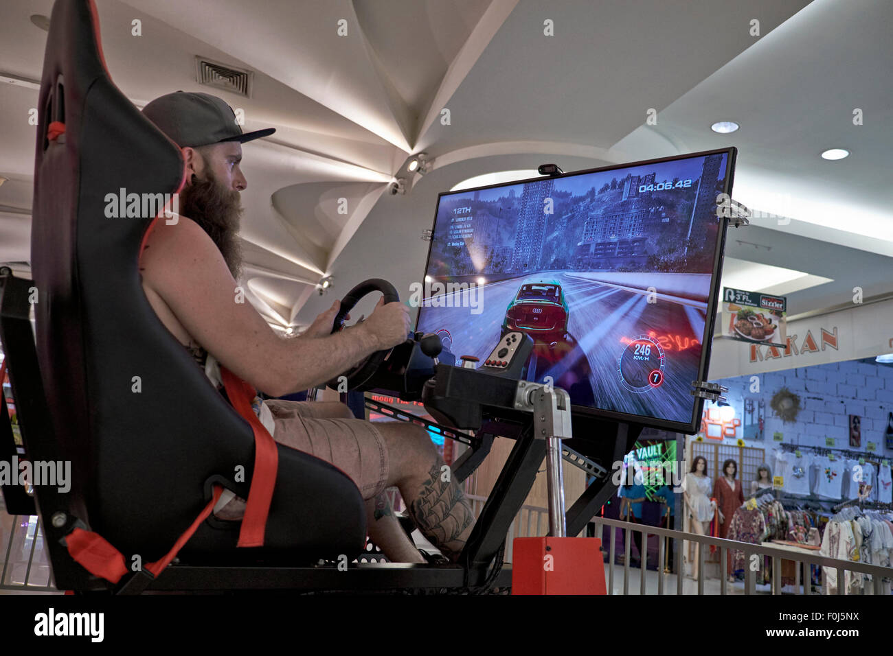 Person playing a Virtual Reality motor racing game. Ripley's Believe it or Not Pattaya Thailand. - Stock Image