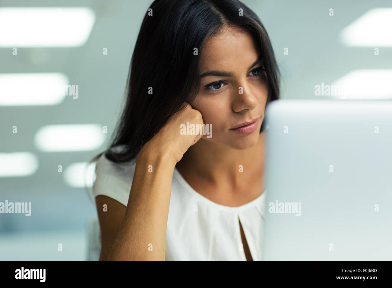 Portrait of a young beautiful businesswoman working on laptop in office - Stock Image