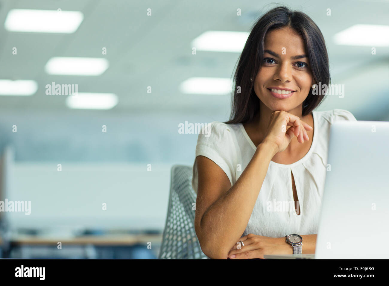 Portrait of a smiling businesswoman working in office - Stock Image
